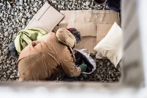 A top view of homeless beggar man with belongings outdoors in city.